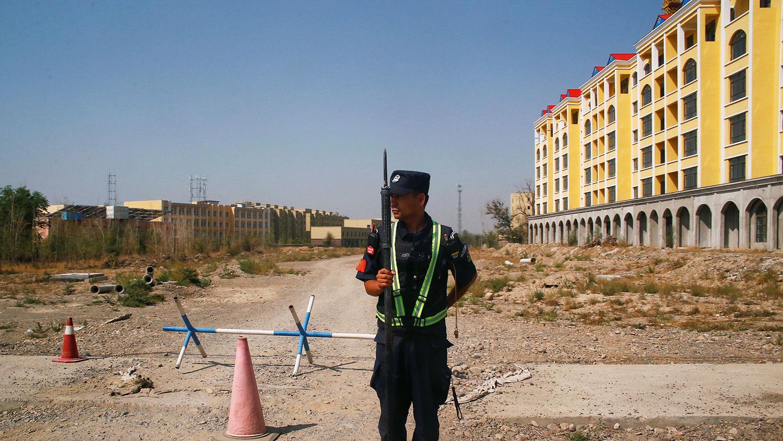 中国新疆维吾尔自治区伊宁市一家职业教育中心附近,一名警察站岗。(路透社)