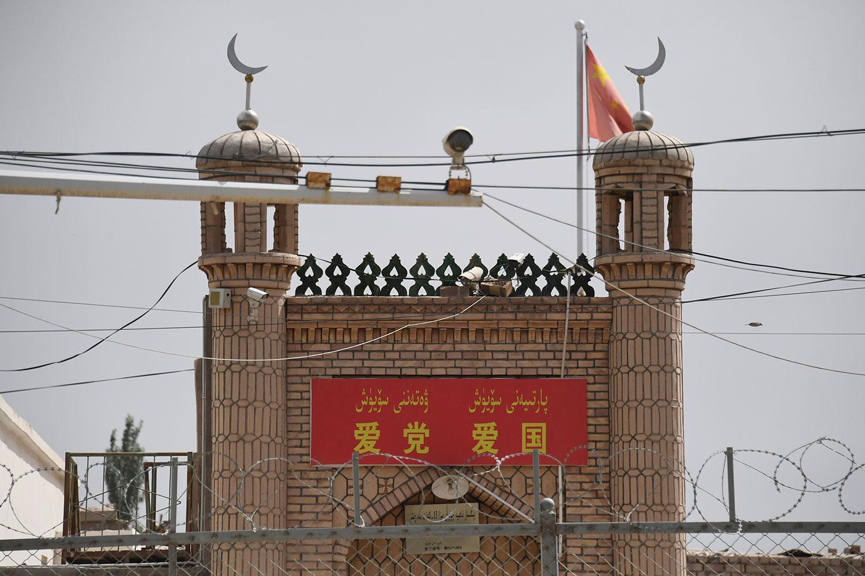 """2019年6月4日,在新疆喀什市一座清真寺入口上面写着""""爱党爱国""""标语。(法新社)"""