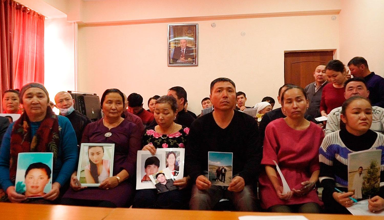2018年12月7日,哈萨克斯坦阿拉木图的一中国哈萨克斯坦倡导组织的办公室里,人们手举在新疆失踪亲属的照片。(美联社)
