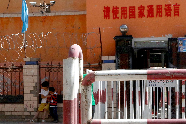 """2018年8月31日,孩子们在新疆一所学校的入口外玩耍,周围有铁丝网,路障和监控摄像机,标语上写着:""""请使用国家的通用语言"""",表明使用普通话。(美联社)"""