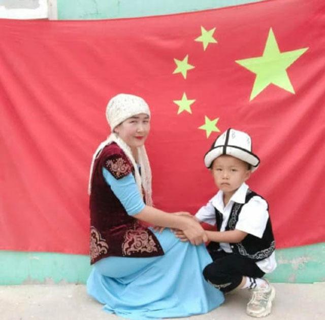 伊犁尼勒克县一哈萨克族妇女与孩子在中国旗前拍照。(乔龙提供)