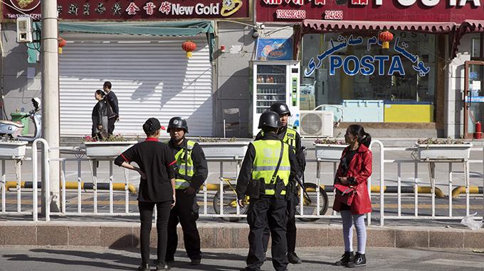 正在对行人进行检查的新疆警察(美联社)
