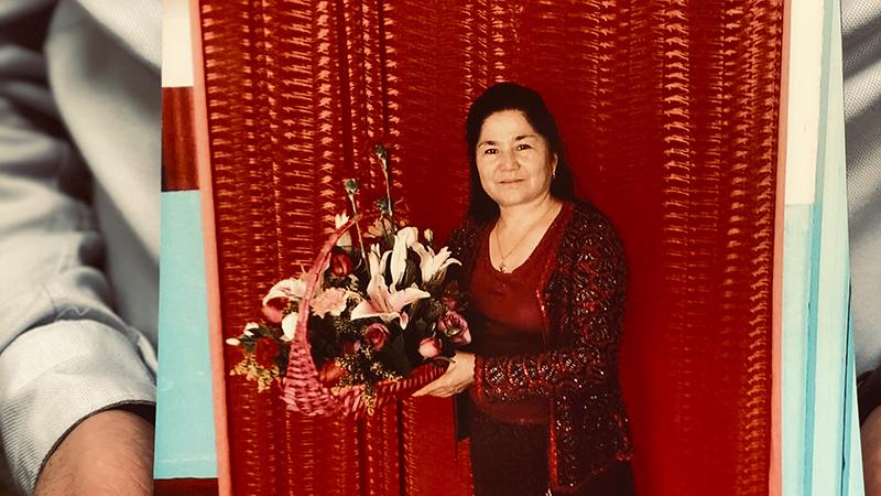 流亡美国的维吾尔人权活动人士乔达特(Ferkat Jawdat)手捧着的母亲画像(美联社)
