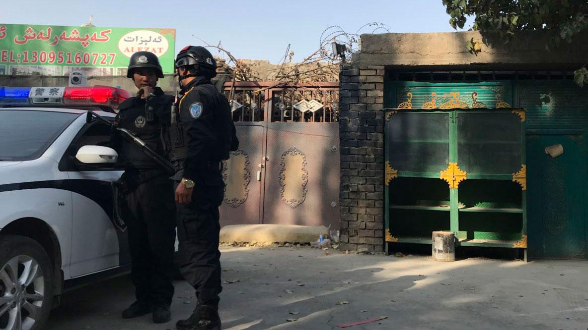 图为2017年11月2日,在新疆库尔勒市,警察站在再教育中心的附近。(AP)