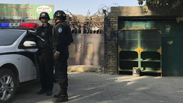 """资料图片:警察在新疆一所""""再教育营""""前巡逻(美联社)"""
