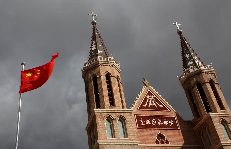 图为河北省黄土岗村的天主教堂前飘扬的中国国旗。(路透社)