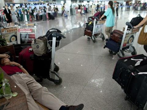 北京机场内的旅客在休息候机。(美联社)