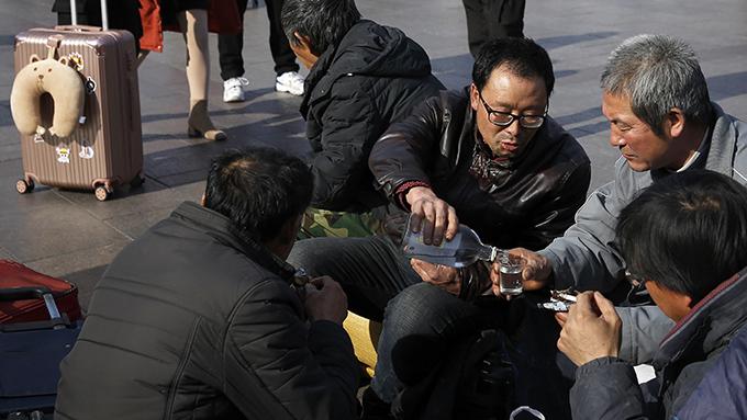 2019年1月26日在北京站外等车的几名农民工(美联社资料图)