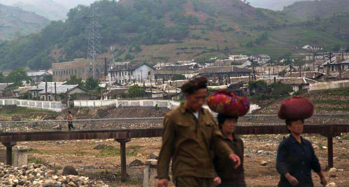 资料图片:朝鲜居民沿朝鲜咸镜北道的金策镇沿河而行。(美联社)