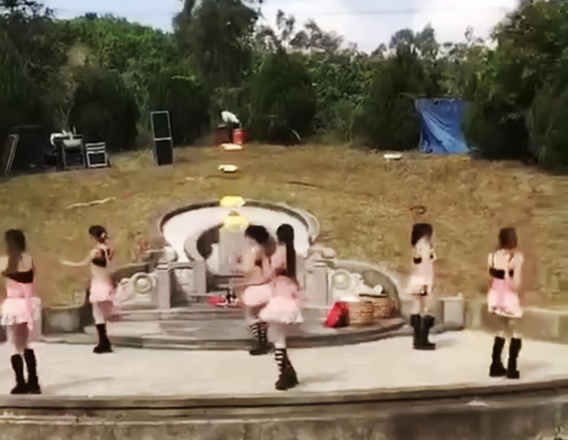 """中国墓地价格一路飙升。图为中国一处墓地请来年轻女子""""环保扫墓""""。(网络视频截图)"""