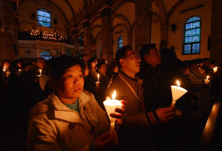 图片:2013年3月30日,在北京的一间教堂内,中国天主教徒们举蜡烛祈祷。(资料图片/法新社)