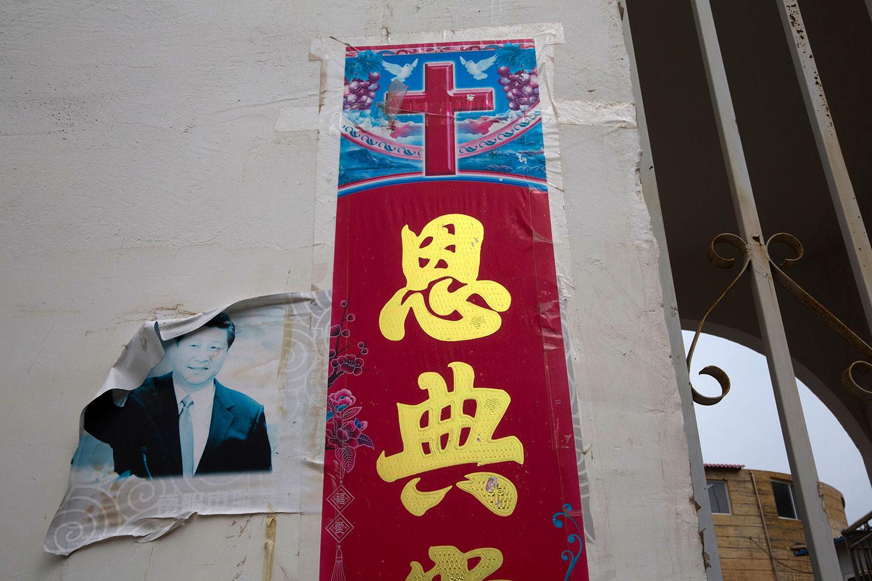 资料图片:2018年6月1日,河南省南阳市一座家庭教堂外的基督教海报附近,一张褪色的习近平照片。(美联社)