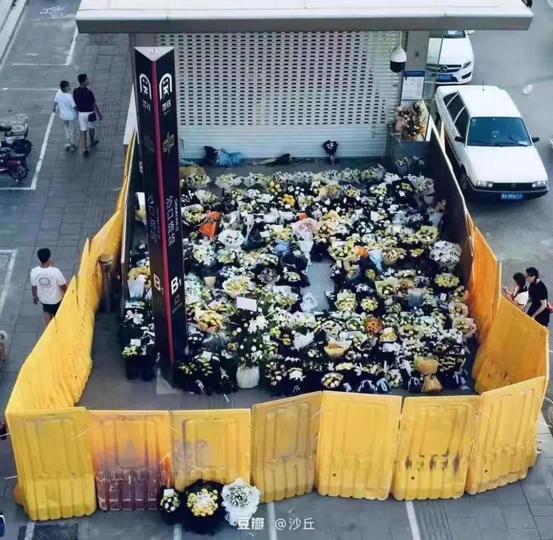 """郑州地铁五号线洪灾遇难者""""头七"""",家属和居民鲜花被当局用黄色板围住,阻止民众围观。(微博图片)"""