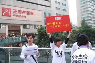 """图片:11月5日,由爱白成都青年同志活动中心联合成都九个高校社团组织共同发起""""收集微笑""""活动,反对歧视艾滋病人。(爱白网)"""