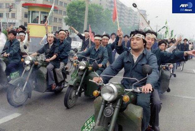 1989年5月18日,以个体户为主的北京民众组成摩托车队声援绝食学生。北京戒严后,摩托车队称为飞虎队,四处传播军队进城消息,呼吁民众前往拦阻。其成员很多在六四后被判重刑。( 吴仁华@wurenhua/AFP )
