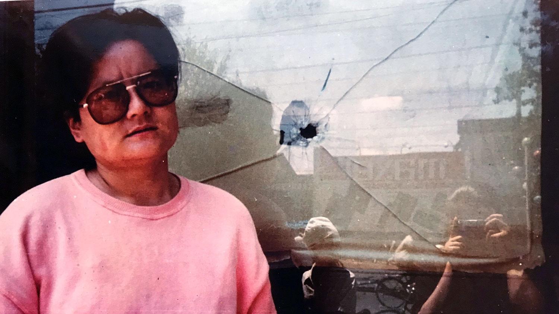 王丽玲摄于1989年六四后西单一家商店被子弹打穿的窗前。(王丽玲提供)