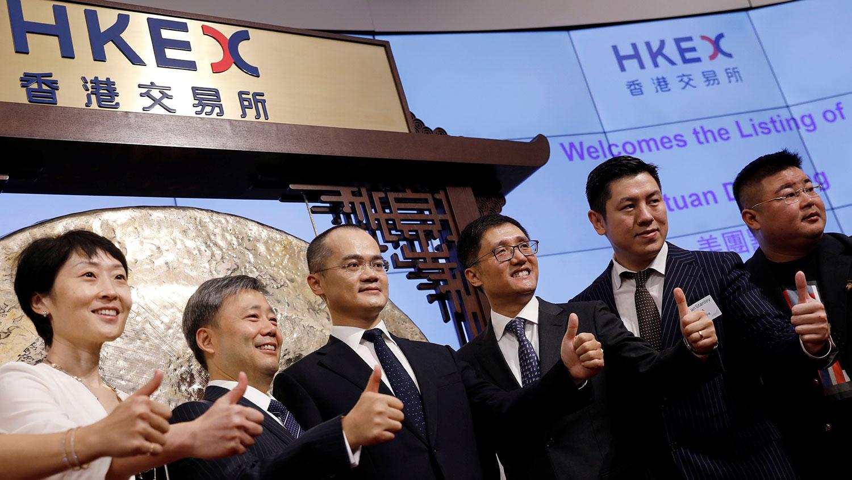 2018年9月20日,美團點評的聯合創始人,董事長兼首席執行官王興(左三)於在香港的香港交易所。(路透社)