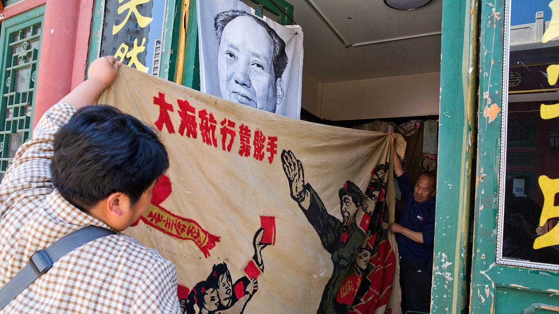 """当局利用毛左肯定文革 但压制其行动。图为民众展开了 1969 年的横幅,描绘了中国前领导人毛泽东""""视察文革大军""""和""""大海航行靠舵手""""的标语。(美联社图片)"""