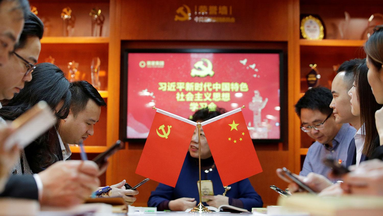 """资料图片:北京潮星控股集团有限公司员工拿着智能手机在""""学习强国""""平台上交流习近平的讲话和《习近平新时代中国特色社会主义思想》的理论学习。(路透社)"""