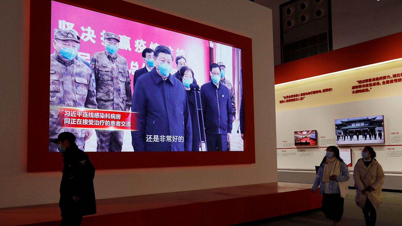 2020 年 12 月 31 日,在武汉会展中心举办的抗击冠状病毒病疫情展览,参观者走近展示习近平的屏幕。 (路透社)