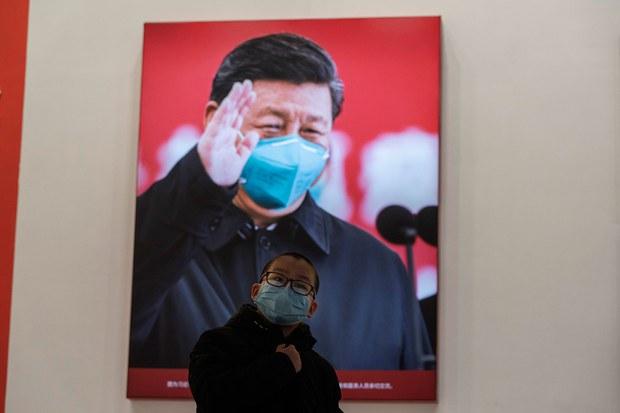 中国2020舆论宣传大拐弯 只有他是不变量。图为,   2021年1月23日,湖北省武汉市抗击冠状病毒展览会上,一名戴着口罩的孩子在习近平照片旁。