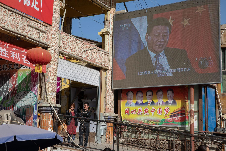 2017年11月3日,在中国新疆和田市集贸市场附近的屏幕上的习近平,下方宣传标语:同心共筑中国梦。 (美联社图片)