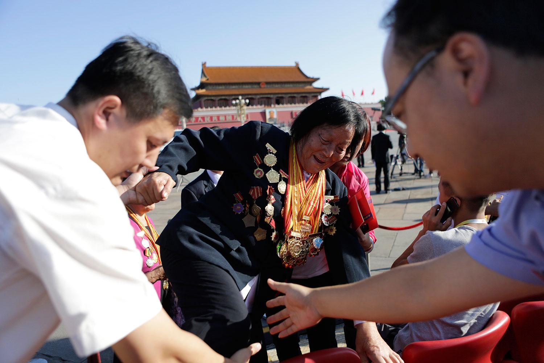 2015年9月3日,佩戴徽章和勋章的申纪兰,在北京举行纪念第二次世界大战结束70周年阅兵式前,工作人员帮助她入座。(美联社)