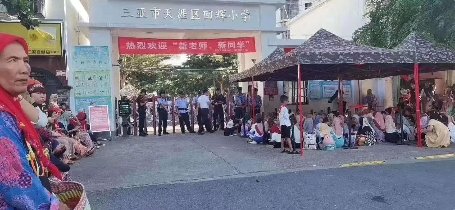海南省三亚市回辉小学门口,回辉女学生戴头巾坐在地上。(推特图片/乔龙提供)