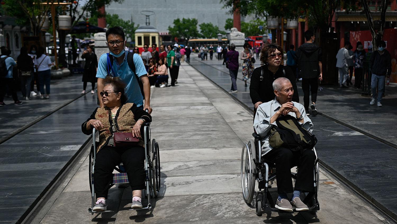 2021年5月11日,在北京的一条街道上,一名老年男女坐着轮椅。 (法新社)