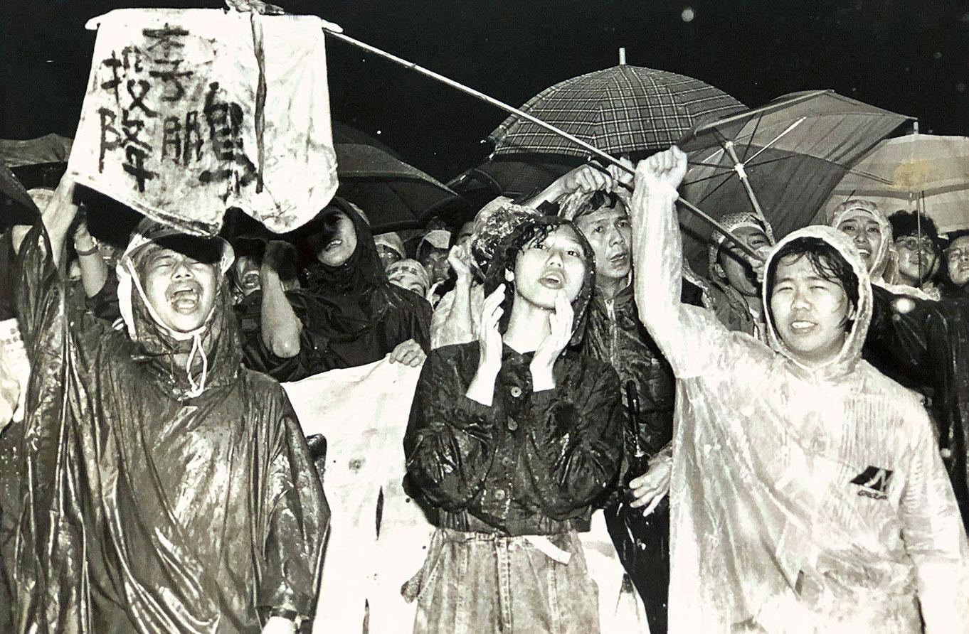 """1989年5月20日,学生们集会抗议中国总理李鹏,横幅写着""""投降,李鹏""""。(美联社)"""