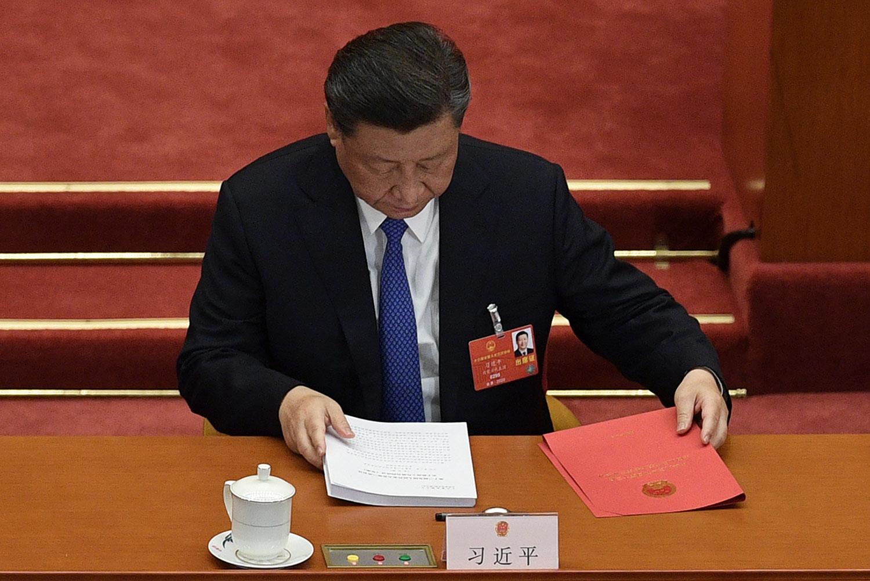 图为,2020年5月28日,习近平在北京人民大会堂举行的全国人民代表大会闭幕会议时准备文件。(法新社)