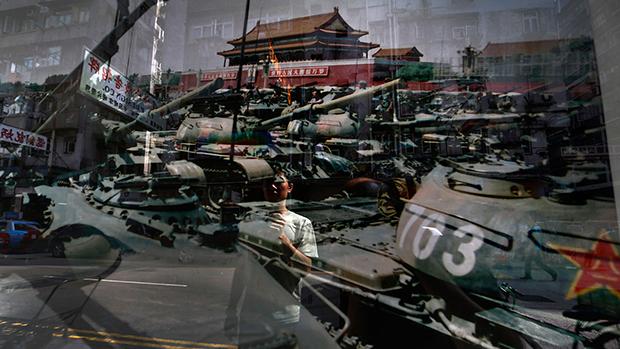 一名男子正在观看1989年6月4日摄于北京天安门广场的一张照片 (美联社资料图)