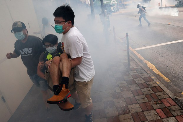 """2020年5月24日下午,大批民众在铜锣湾发起""""反恶法大游行"""",警方则以水炮车和催泪瓦斯驱散示威人群,并且有百多人遭到拘捕。(法新社)"""