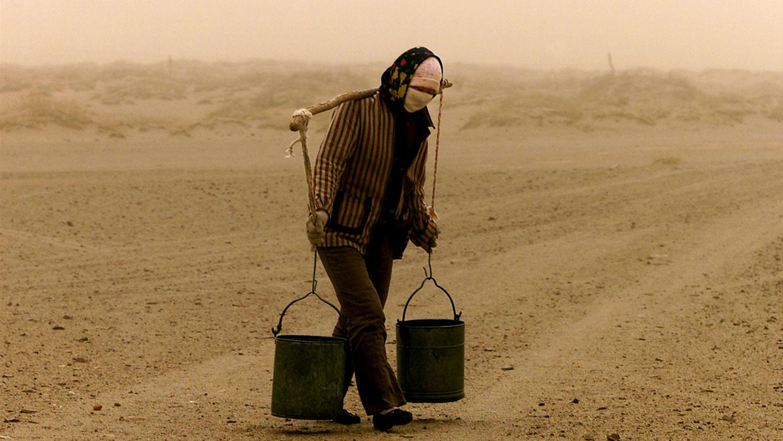 图为,在内蒙古自治区锡林郭勒盟以北约50公里(31英里),一名妇女将水挑回家。(路透社)
