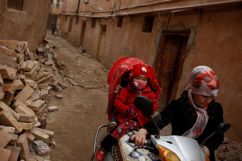 """新华社今年7月曾专文介绍喀什古城如何""""换新"""",变身国家5A旅游景区。喀什地区拆千年土房、盖""""新的古城"""",是摧毁维吾尔人的文化根基。图为,新疆维吾尔自治区喀什市古城区,一名妇女将摩托车推过小巷时,孩子们坐在踏板车的后方。(路透社)"""