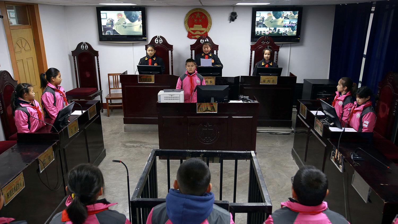 图为,2018年12月3日,在新疆维吾尔自治区阿克苏州举行的为期一周的中国宪法日宣传活动中,小学生参加了法庭审判模拟。(路透社)