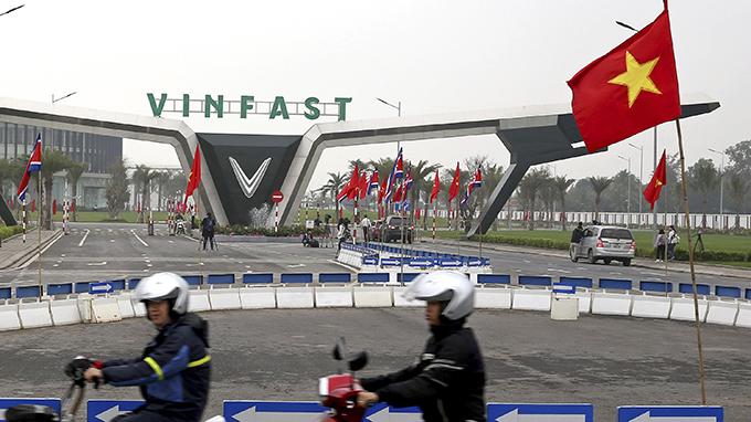 飘扬在越南一家工厂外的越南国旗(美联社)
