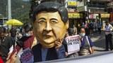 """印度达兰萨拉的流亡藏族民众在2020中国国庆日期间抗议。图为一名男子举着中国国家主席习近平的面具,旁边标语写着""""习近平,为你感到羞耻""""。(美联社)"""