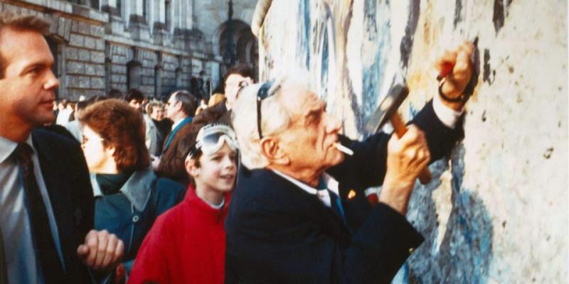 """美国著名指挥家伯恩施坦(Leonard Bernstein)借赴柏林指挥""""自由颂""""的机会,到柏林墙庆祝自由,并敲下这堵象征专制奴役的大墙的残片。(Public Domain)"""