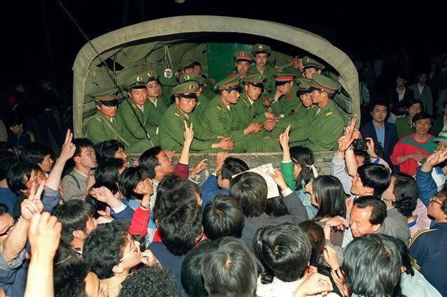 被阻止前行的军车上,军人目光木纳,而车下百姓群情激愤:你们明白真相吗?(Public Domain)
