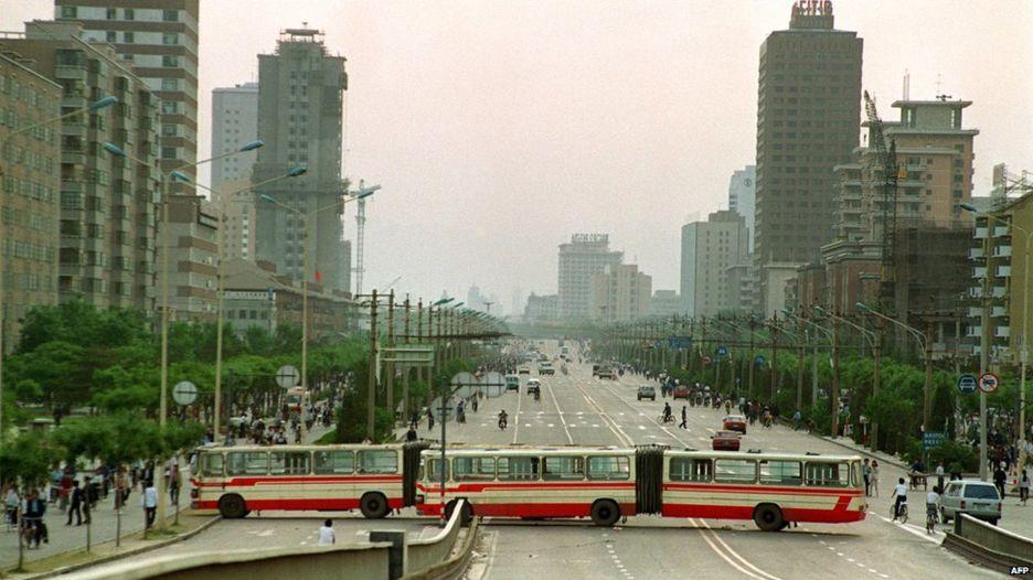 长安街上,人们用大客车和隔离墩阻挡长驱直入的军车。(Public Domain)