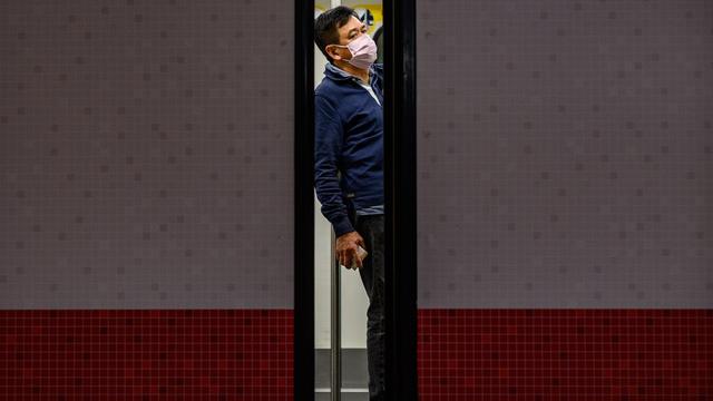 香港新冠肺炎病例不断增加,一名男子戴着口罩搭乘地铁。(法新社)