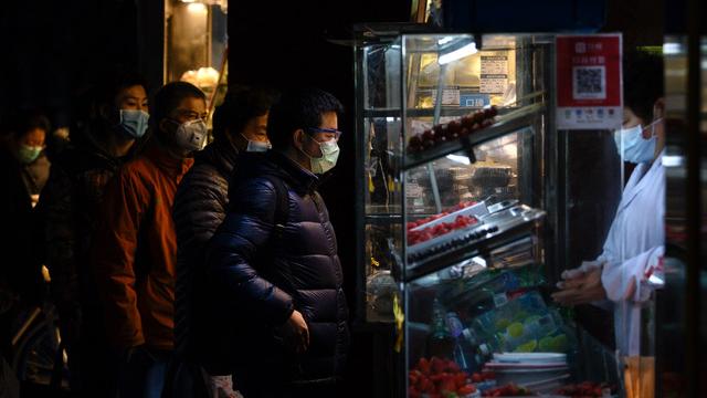 几名上海民众戴着口罩排队购买餐点。(法新社)
