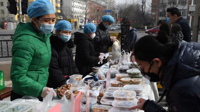 北京一家餐馆在餐厅外面贩售外带餐点,新冠肺炎疫情已对许多生意造成影响。(法新社)