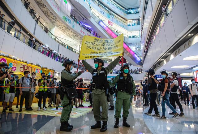 香港警察在一商场内举黄旗警告。(法新社)