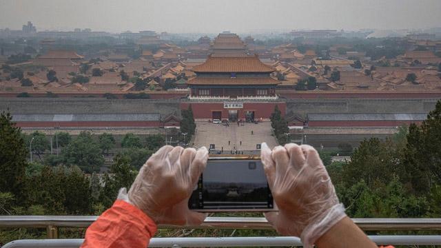陈冠中的小说探讨北京城变迁,正史、野史虚实交错。图为民众从景山顶上俯瞰紫禁城,照片左上方远处为北京饭店。(美联社)