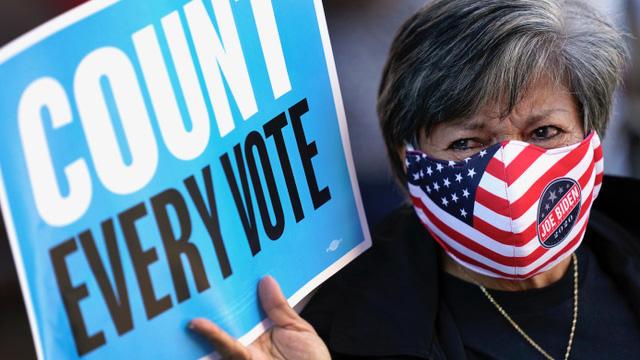 特朗普与拜登竞争激烈,计票工作耗时,一位选民举牌主张每张选票都应计入。(美联社)
