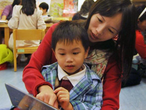 图为一个母亲和儿子在台北公立图书馆读书。(AFP)
