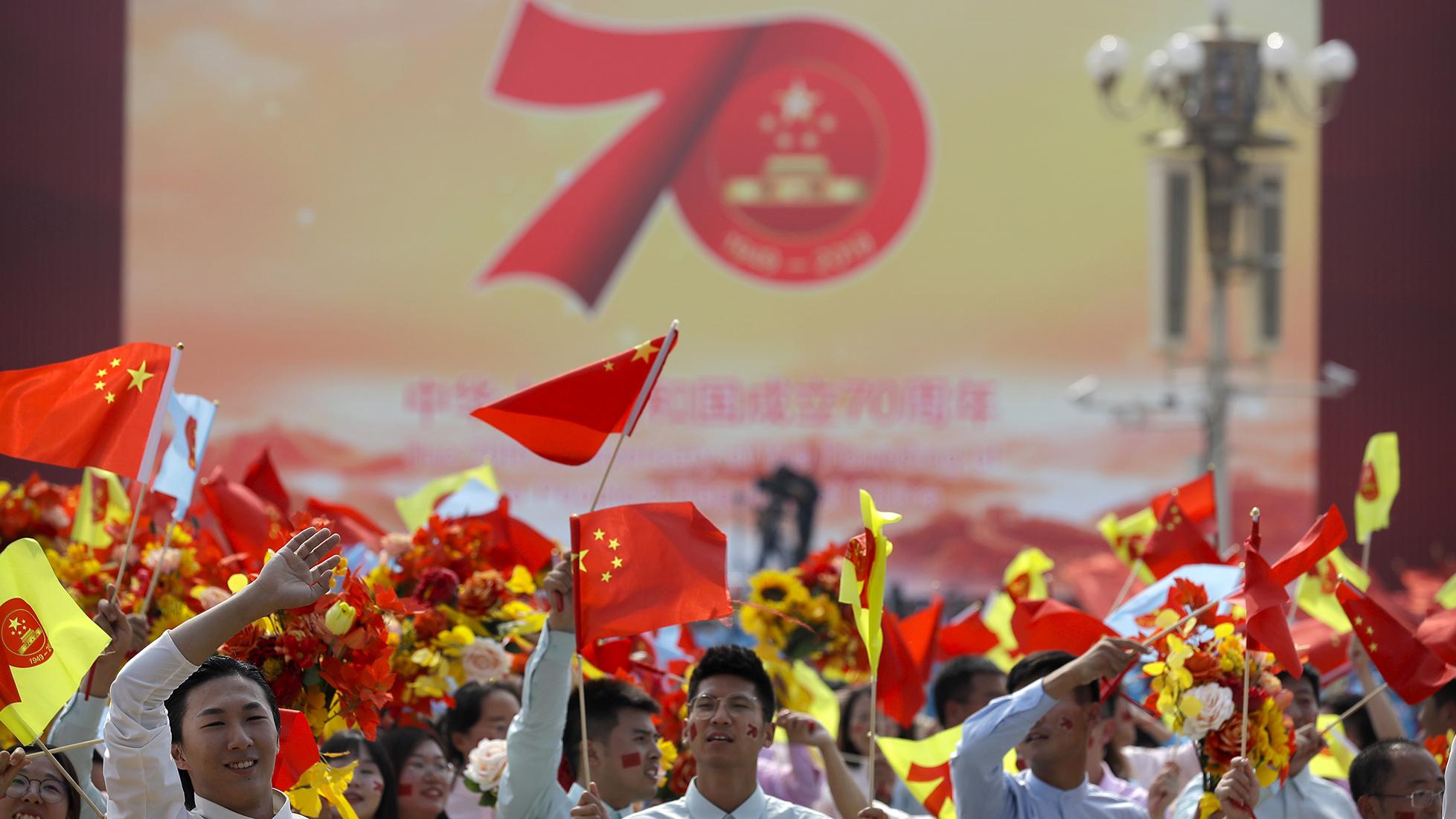 中国国庆70周年上的学生们在挥舞国旗。(美联社)