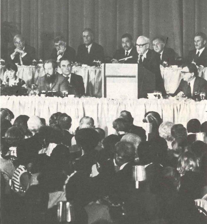 1975年6月30日索尔仁尼琴在华盛顿市区劳联产联大会上应邀演讲。图为劳联产联主席乔治·米尼(右四站立者)向与会者介绍索尔仁尼琴(左三)的意义。图片截自AFL-CIO Free Trade Union News/ Published by Department of International Affairs, AFL-CIO Vol. 30, No.7-8 July –August 1975